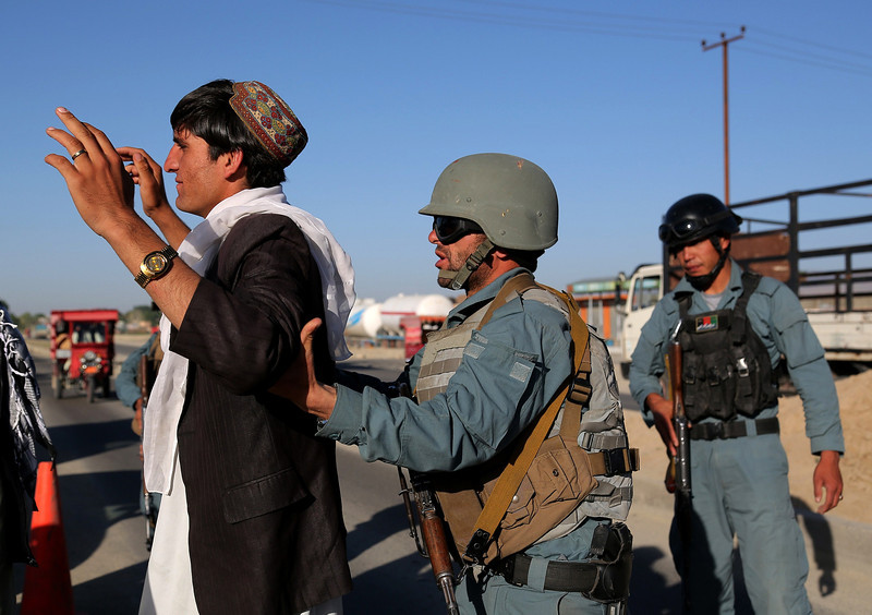 Description of  An Afghan policeman searches a vehicle passenger at a checkpoint in Ghazni province on May 27, 2014. Afghan presidential candidates Abdullah Abdullah and Ashraf Ghani will compete in a run-off on June 14, to determine who leads Afghanistan into a new era without the assistance of NATO combat troops to help fight the Taliban insurgency. Rahmatullah Alizadah/AFP/Getty Images