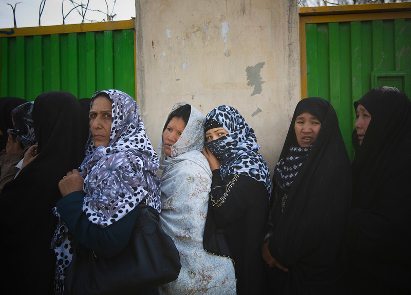 Description of  Afghan women queue outside a school to get their registration card on the last day of voter registration for the upcoming presidential elections outside a school in Kabul, Afghanistan, Tuesday, April 1, 2014. Elections will take place on April 5, 2014. (AP Photo/Anja Niedringhaus)  - Niedringhaus, 48, was killed and an AP reporter was wounded on Friday, April 4, 2014 when an Afghan policeman opened fire while they were sitting in their car in eastern Afghanistan.