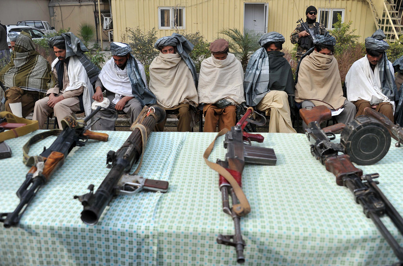 Description of  Former Taliban fighters sit alongside their weapons, prior to handing them over as they join a government peace and reconciliation process at a ceremony in Jalalabad, capital of Nangarhar province on January 19, 2014. NATO formally transferred responsibility for nationwide security to Afghan forces in June 2013. Noorullah Shirzada/AFP/Getty Images