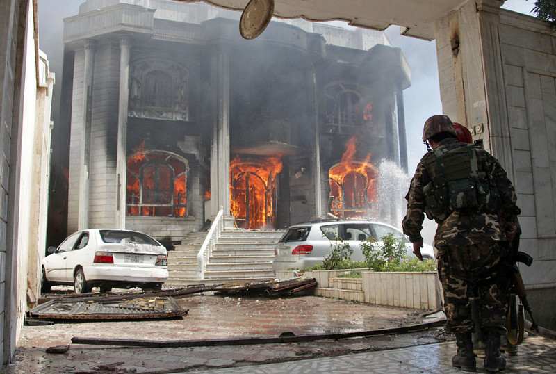 Description of  Afghan security forces watch a house burn at the site of a clash between insurgents and security forces at the Indian Consulate in Herat, Afghanistan, Friday, May 23, 2014. Gunmen armed with machine guns and rocket-propelled grenades attacked the Indian Consulate in western Afghanistan's Herat province Friday, an assault that injured no diplomatic staff, police said. Indian officials said there had been a threat against its diplomats in Afghanistan, but gave no other details. (AP Photo/Hoshang Hashimi)
