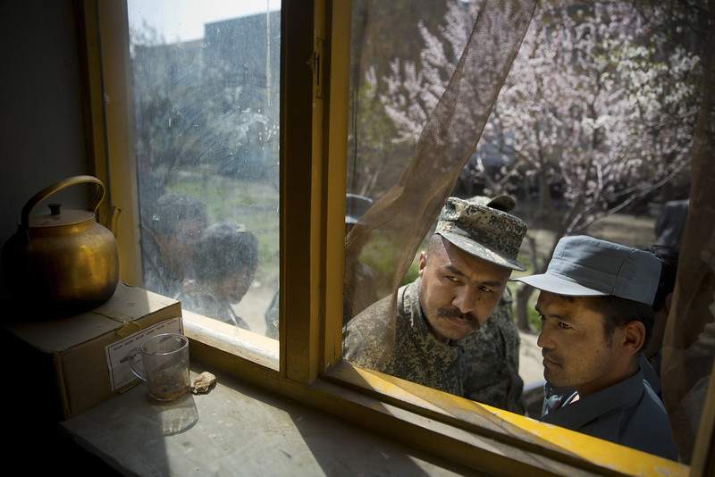 Description of  An Afghan soldier, left, and a police man peek through a window as they queue with others to get their registration card on the last day of voter registration for the upcoming presidential elections outside a school in Kabul, Afghanistan, Tuesday, April 1, 2014. Elections will take place on April 5, 2014. (AP Photo/Anja Niedringhaus)  - Niedringhaus, 48, was killed and an AP reporter was wounded on Friday, April 4, 2014 when an Afghan policeman opened fire while they were sitting in their car in eastern Afghanistan.