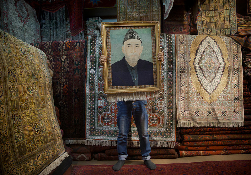 Description of  An Afghan carpet seller holds up a framed carpet depicting Afghan President Hamid Karzai in his store in Kabul, Afghanistan, Sunday, March 30, 2014. Afghans go to the polls April 5, 2014 to choose a new president, and that in itself may one day be considered Karzai's greatest achievement. (AP Photo/Anja Niedringhaus) - Niedringhaus, 48, was killed and an AP reporter was wounded on Friday, April 4, 2014 when an Afghan policeman opened fire while they were sitting in their car in eastern Afghanistan.