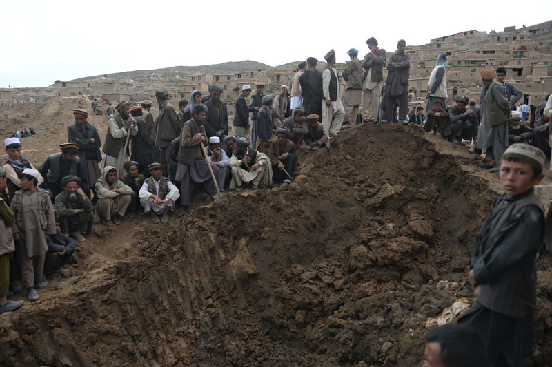 Description of  Afghan rescuers search desperately for survivors trapped under the mud in Argo district of Badakhshan province on May 3, 2014 after a massive landslide May 2 buried a village. Rescuers searched in vain for survivors May 3 after a landslide buried an Afghan village, killing 350 people and leaving thousands of others feared dead amid warnings that more earth could sweep down the hillside. Local people made desperate efforts to find victims trapped under a massive river of mud that engulfed Aab Bareek village in Badakhshan province, where little sign remained of hundreds of destroyed homes. SHAH MARAI/AFP/Getty Images