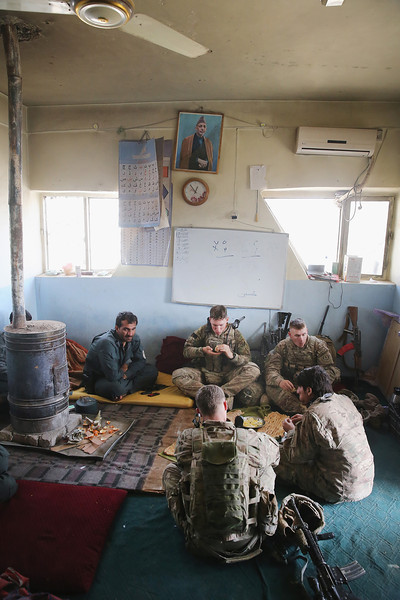 Description of  KANDAHAR, AFGHANISTAN - MARCH 09:  Soldiers with the U.S. Army's 4th squadron 2d Cavalry Regiment eat lunch at an Afghan National Police (ANP) outpost during a patrol on March 9, 2014 near Kandahar, Afghanistan.  U.S. President Barack Obama recently ordered the Pentagon to begin contingency planning for a pullout from Afghanistan by the end of 2014 if Afghanistan President Hamid Karzai or his successor refuses to sign the Bilateral Security Agreement.  (Photo by Scott Olson/Getty Images)