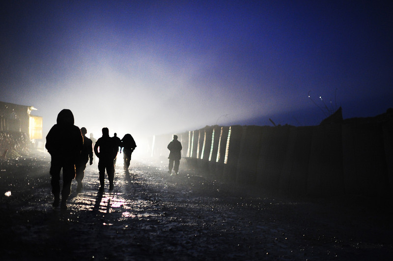 Description of  In this picture taken on March 16, 2014, Afghan soldiers attached to the 4th Brigade, 201 Army Corps of the Afghan National Army (ANA) walk in the rain in the early evening near blast walls inside at a forward operating base in Khogyani district. In the eastern district of Khogyani, the war against Taliban militants is a day-to-day struggle for control of fields and villages just outside Jalalabad, one of Afghanistan's biggest and most strategic cities. ROBERTO SCHMIDT/AFP/Getty Images