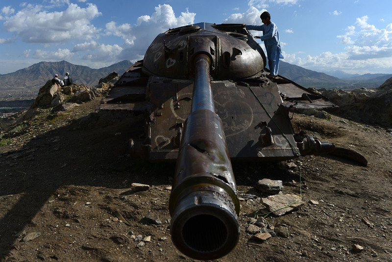 Description of  This photograph taken on May 9, 2014 shows an Afghan youth playing over the remains of a Soviet-era tank, graffitied with heart symbols, at a hilltop near Qargha Lake in the outskirts of Kabul. Afghanistan remains at war, with civilians among the hardest hit as the Taliban wage an increasingly bloody insurgency against the government. WAKIL KOHSAR/AFP/Getty Images