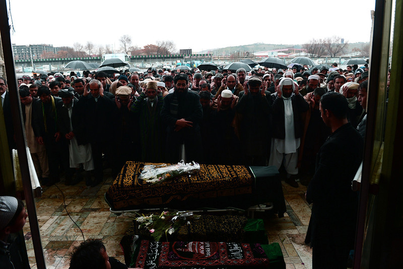 Description of  In this file photograph taken on March 23, 2014, Afghan mourners offer final prayers over the flag-covered coffins of slain AFP reporter Sardar Ahmad, his wife and their two children during his funeral in Kabul.  Six weeks after surviving a Taliban attack on a Kabul hotel that left his father, mother, brother and sister dead, miracle child Abuzar Ahmad, son of slain AFP reporter Sardar Ahmad, arrived in Canada on April 30, 2014 to start his life anew. WAKIL KOHSAR/AFP/Getty Images