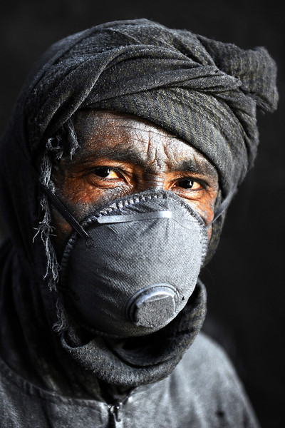 Description of  An Afghan labourer poses at an aluminium workshop in Herat on May 27, 2014. Some 100 people work in the Herat Aluminium factory with around around 70 to 100 tons of aluminium produced each month, with most all of its products used domestically. Aref Karimi/AFP/Getty Images