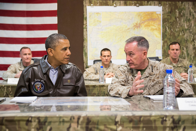 Description of  President Barack Obama gets a briefing by Marine General Joseph Dunford, commander of the US-led International Security Assistance Force (ISAF), right, after arriving at Bagram Air Field for an unannounced visit, on Sunday, May 25, 2014, north of Kabul, Afghanistan. (AP Photo/ Evan Vucci)