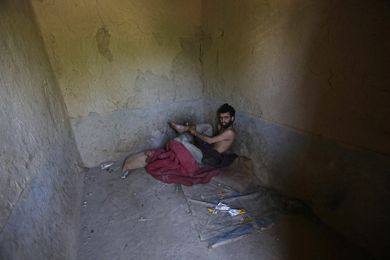 Description of  Mahdi, 27, a drug addict, is bound in a cell in his 40-day incarceration at the Mia Ali Baba shrine in Jalalabad, Afghanistan, Thursday, May 1, 2014. It is believed locally that 40 days of chaining to a wall with a restricted diet at the 300-year old shrine can cure the mentally ill, drug addicts and those possessed by spirits. If a shrine keeper decides their situation is improving, they may be unchained for a few minutes. However, shrines such as Mia Ali Baba are frowned upon by health care professionals and other critics who say the remedy is ineffective and that those who run the incarceration prey on vulnerable people's religious beliefs and superstitions to make a profit. (AP Photo/Rahmat Gul)