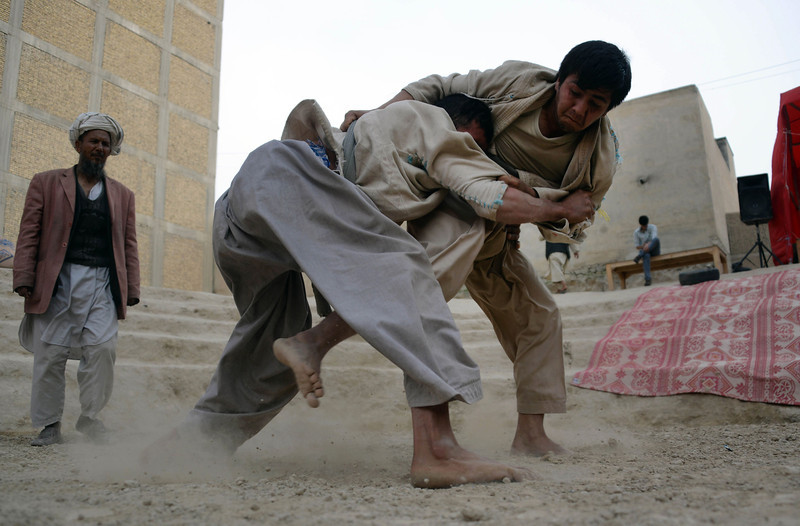 Description of  Afghan wrestlers compete at an outdoor arena in the northern town of Mazar-i-Sharif on April 29, 2014. Wrestling is a popular sport in Afghanistan, and is traditionally practiced among poorer members of Afghan society. FARSHAD USYAN/AFP/Getty Images