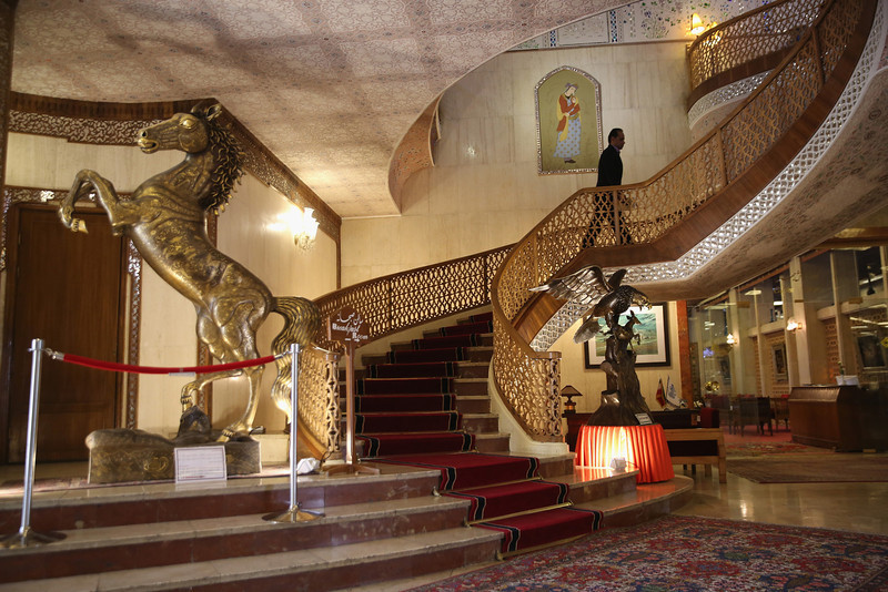 Description of  ISFAHAN, IRAN - JUNE 03:  An employee walks up a grand staircase in the lobby of the Abbasi Hotel on June 3, 2014 in Isfahan, Iran. On Iran on June 4, will mark the 25th anniversary of the death of the Ayatollah Khomeini and his legacy of the Islamic Revolution.  (Photo by John Moore/Getty Images)