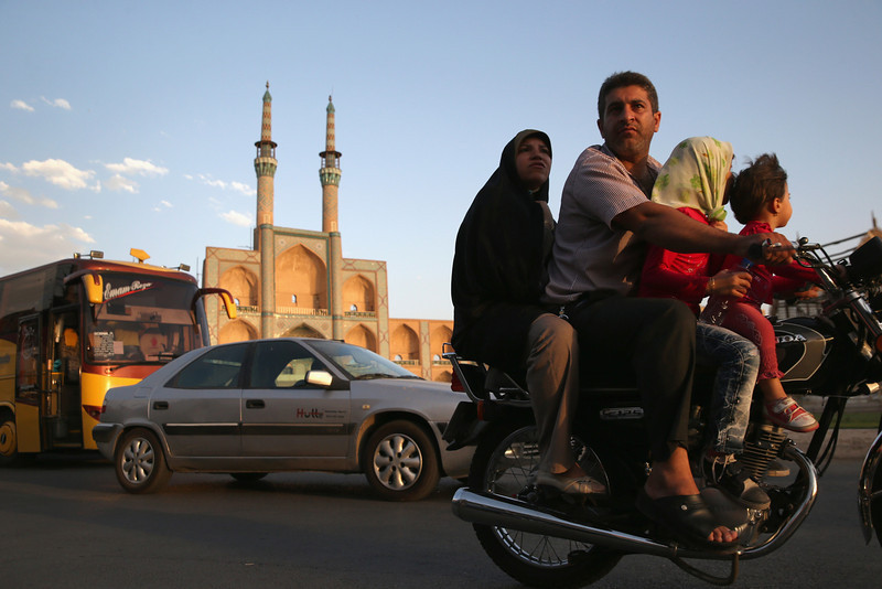 Description of  YAZD, IRAN - JUNE 01:  A family rides a motorcycle past the Amir Chakhmaq Hosseinieh worship site, one of the largest such structures in Iran, on June 1, 2014 in the desert town of Yazd, Iran. On June 4, Iran marks the 25th anniversary of the death of the Ayatollah Khomeini and the legacy of his Islamic Revolution.  (Photo by John Moore/Getty Images)