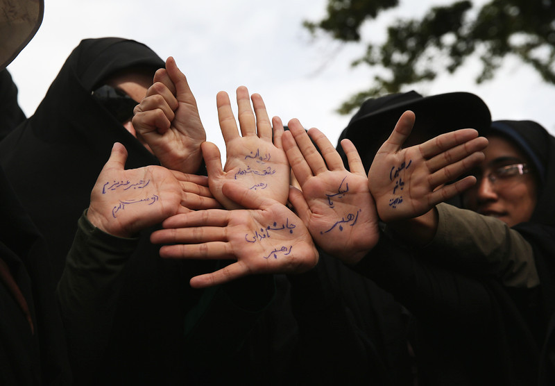 Description of  TEHRAN, IRAN - JUNE 04:  Women hold up their hands pledging to offer their lives, if needed, for the Islamic Revolution outside the shrine of the Ayatollah Khomeini on the 25th anniversary of his death on June 4, 2014 on the outskirts of Tehran, Iran. Thousands of people gathered to hear speeches to mark the event. Khomeini, the founder of the Islamic Republic, is still revered by many Iranians, and his portrait hangs throughout the country.  (Photo by John Moore/Getty Images)