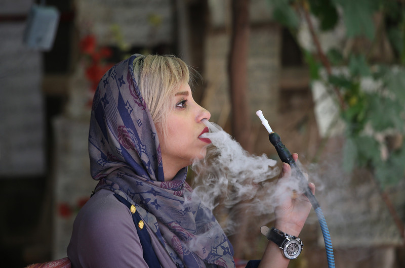 Description of  SHIRAZ, IRAN - MAY 29:  A woman smokes a hookah while visiting a poetry calligraphy workshop on May 29, 2014 in Shiraz, Iran. Shiraz, celebrated for more than 2,000 years as the heartland of Persian culture, is known as the home of Iranian poetry and for its progressive attitudes and tolerance. Like all of Iran, this week Shiraz observes the 25th anniversary of the death and continued legacy of the Ayatollah Khomeini, the father of the Islamic revolution.  (Photo by John Moore/Getty Images)