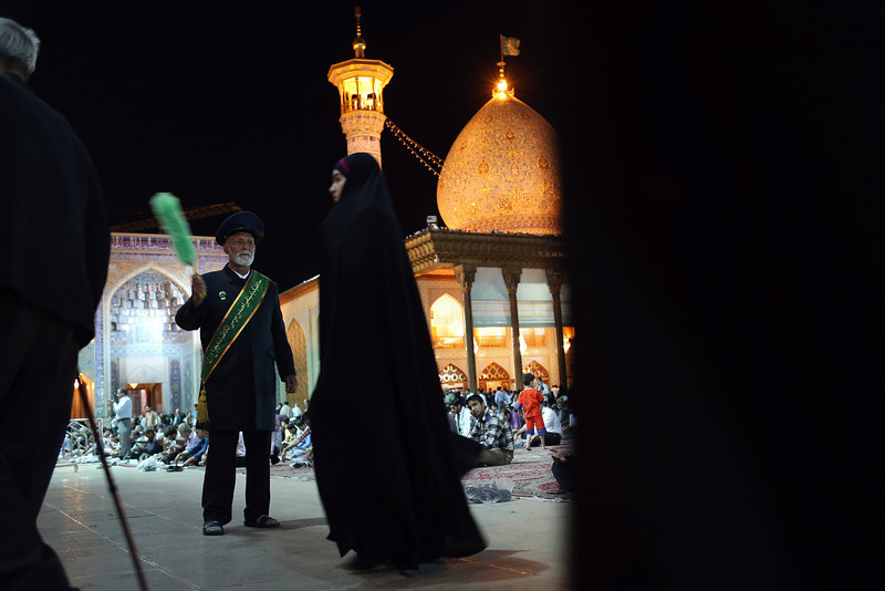 Description of  SHIRAZ, IRAN - MAY 29:  A crowd-control volunteer waves a feather duster the Aramgah-e Shah-e Cheragh shrine on May 29, 2014 in Shiraz, Iran. Thousands of Muslim pilgrims visit to pray at the shrine, one of the holiest Shiite sites in Iran. Shiraz, celebrated for more than 2,000 years as the heartland of Persian culture, is known as the home of Iranian poetry and for its tolerant and progressive culture. Like all of Iran, this week Shiraz observes the 25th anniversary of the death and continued legacy of the Ayatollah Khomeini, the father of the Islamic revolution.  (Photo by John Moore/Getty Images)
