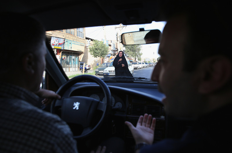 Description of  YAZD, IRAN - JUNE 01:  A driver and translator drive pass pedestrians on June 1, 2014 in Yazd, Iran. The old city of Yazd is considered one of the oldest towns on earth, according to UNESCO. (Photo by John Moore/Getty Images)