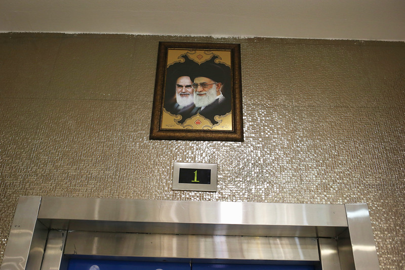 Description of  ISFAHAN, IRAN - JUNE 02:  Portraits of  the late Ayatollah Khomeini (L) and Iran's current supreme leader Ayatollah Khamenei gaze hang over an elevator in the new Isfahan City Center shopping mall on June 2, 2014 in Isfahan, Iran. The mall complex, still under construction, is the largest shopping center in Iran and will include a 5-star hotel, a financial center and an entertainment center with cinema and fair complex. The mall is being built by Prestige Land Iran and was designed by architect Madardo Cadiz of Cadiz International. Historic Isfahan, with it's immense mosques, picturesque bridges and ancient historic bazaar, is a virtual living museum of Iranian traditional culture. It's also the Iran's top tourist destination for both Iranian and domestic visitors. On June 4 Iran marks the 25th anniversary of the death of the Ayatollah Khomeini and his legacy of the Islamic Revolution.  (Photo by John Moore/Getty Images)