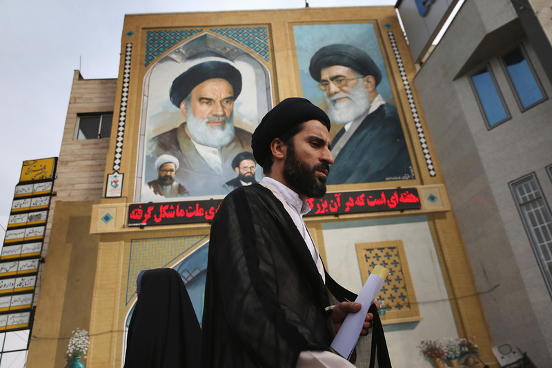 Description of  QOM, IRAN - JUNE 03:  An Islamic Mullah walks past a portrait of the late Ayatollah Khomeini on June 3, 2014 in Qom, Iran. Iran is marking the 25th anniversary of the death of the Ayatollah Khomeini and his legacy of the Islamic Revolution.  (Photo by John Moore/Getty Images)
