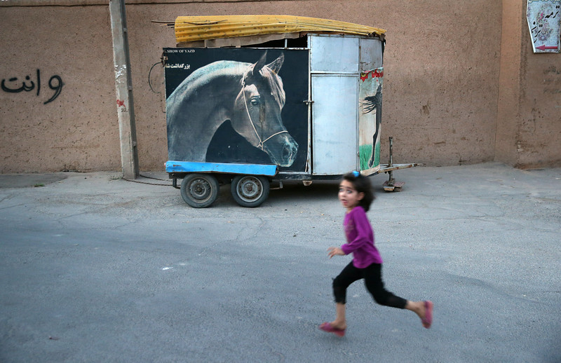Description of  YAZD, IRAN - JUNE 01:  A girl runs past a horse trailer in the old city on June 1, 2014 in the desert town of Yazd, Iran. On June 4, Iran marks the 25th anniversary of the death of the Ayatollah Khomeini and the legacy of his Islamic Revolution.  (Photo by John Moore/Getty Images)