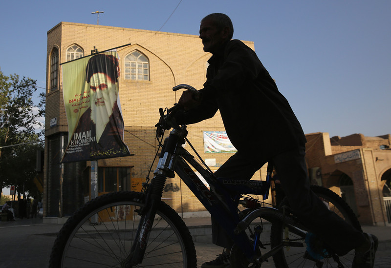 Description of  YAZD, IRAN - JUNE 01:  A cyclist passes a banner featuring the Ayatollah Khomeini on June 1, 2014 in the desert town of Yazd, Iran. On June 4, Iran marks the 25th anniversary of Khomeini's death and the legacy of his Islamic Revolution.  (Photo by John Moore/Getty Images)