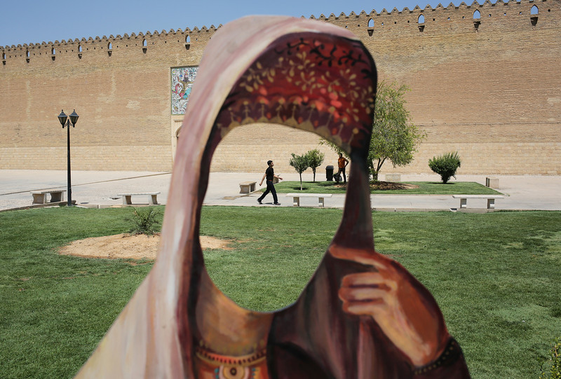 Description of  SHIRAZ, IRAN - MAY 29:  A cutout of a woman in Iranian dress stands in front of the Karim Khani Palace, also a former prison, on May 29, 2014 in Shiraz, Iran. Shiraz, celebrated for more than 2,000 years as the heartland of Persian culture, is known as the home of Iranian poetry and for its progressive attitudes and tolerance. Like all of Iran, this week Shiraz observes the 25th anniversary of the death and continued legacy of the Ayatollah Khomeini, the father of the Islamic revolution.  (Photo by John Moore/Getty Images)