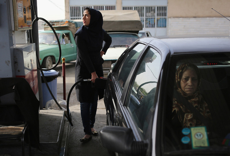Description of  SHAHINSHAHR, IRAN - JUNE 03:  A woman fills her gas tank at a service station on June 3, 2014 in Shahinshahr, Iran. Gas prices, which are regulated by the Iranian government, have risen sharply in the last month. Iran on June 4, will mark the 25th anniversary of the death of the Ayatollah Khomeini and his legacy of the Islamic Revolution.  (Photo by John Moore/Getty Images)