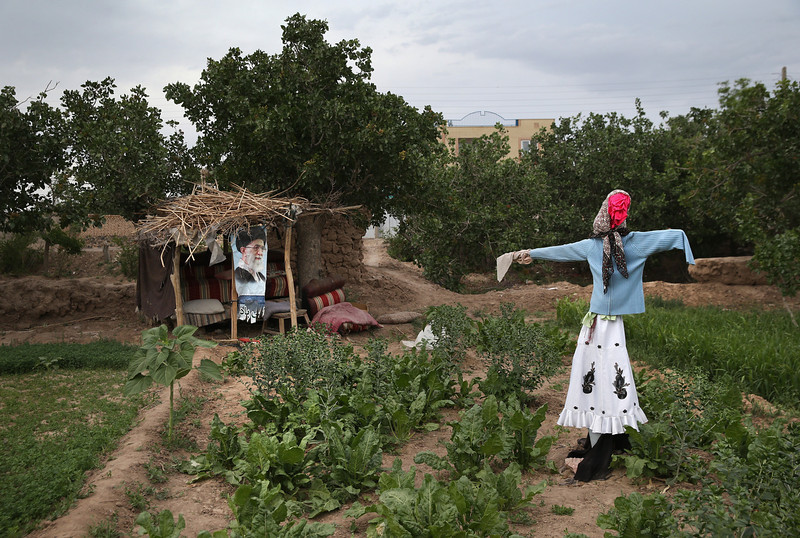 Description of  NARIN, IRAN - JUNE 01:  A scarecrow stands vigil over a backyard garden, as does a photo of Iran's current supreme leader Ayatollah Ali Kamenei on June 1, 2014 in Narin, in central Iran. Narin, known for its mud brick architecture and handicrafts, has been a prominent stop on trade routes since the Sassanid era. On June 4 Iran marks the 25th anniversary of the death of the Ayatollah Komeini and his Islamic Revolution. (Photo by John Moore/Getty Images)