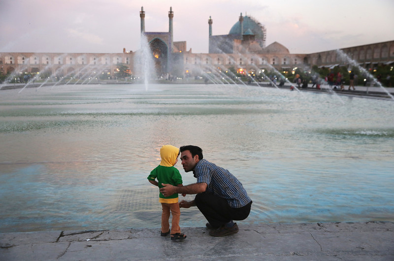 Description of  ISFAHAN, IRAN - JUNE 02:  A father and son spend dusk together in the Unesco-listed Naqsh-eJanan Square on June 2, 2014 in Isfahan, Iran. Isfahan, with it's immense mosques, picturesque bridges and ancient bazaar, is a virtual living museum of Iranian traditional culture. It's also the Iran's top tourist destination for both Iranian and domestic visitors. On June 4, Iran marks the 25th anniversary of the death of the Ayatollah Khomeini and his legacy of the Islamic Revolution. Naqsh-eJanan Square is the second largest square on earth after Tiananmen Square in Beijing.  (Photo by John Moore/Getty Images)