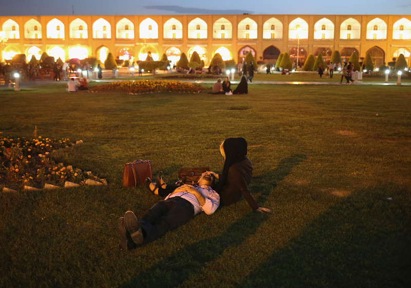 Description of  ISFAHAN, IRAN - JUNE 02:  A couple lies in the Unesco-listed Naqsh-eJanan Square on June 2, 2014 in Isfahan, Iran. Isfahan, with it's immense mosques, picturesque bridges and ancient historic bazaar, is a virtual living museum of Iranian traditional culture. It's also the Iran's top tourist destination for both Iranian and domestic visitors. On June 4, Iran marks the 25th anniversary of the death of the Ayatollah Khomeini and his legacy of the Islamic Revolution. Naqsh-eJanan Square is the second largest square on earth after Tiananmen Square in Beijing.  (Photo by John Moore/Getty Images)