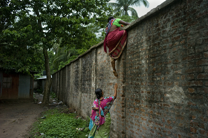 Description of  Hili, West Bengal, India, on the border with Bangladesh. Between rounds by the Border Security Force, two Bangladeshi women cross the wall between the countries. They enter the country empty-handed and leave laden down with smuggled goods. Indian BSF troops accuse the Bangladeshi border guards of letting them through, thus forcing the BSF troops to take more violent action.<br />© Gaël Turine / Agence VU'