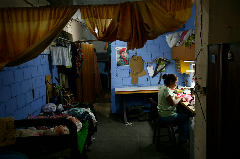 Description of  A woman sewing in a workshop set up inside her apartment. © Jorge Silva / Reuters