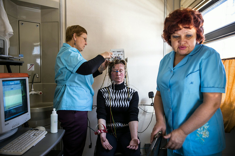 Description of  A doctor and nurse on board the Matvey Mudrov recording an electroencephalogram of Nadegda Gaskevitch who struck her head in a fall in 2003 and now needs regular treatment. © William Daniels / Panos Pictures / National Geographic Magazine