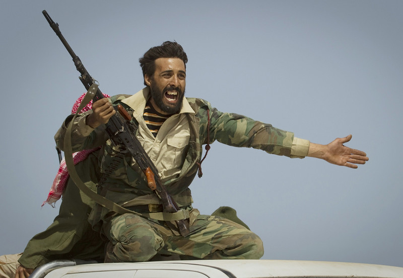 Description of  A Libyan rebel urging people to leave as shells fired by Gadhafi's forces landed on the front outside Bin Jawaad, 150 km east of Sirte. Central Libya, March 29, 2011. © Anja Niedringhaus / Associated Press