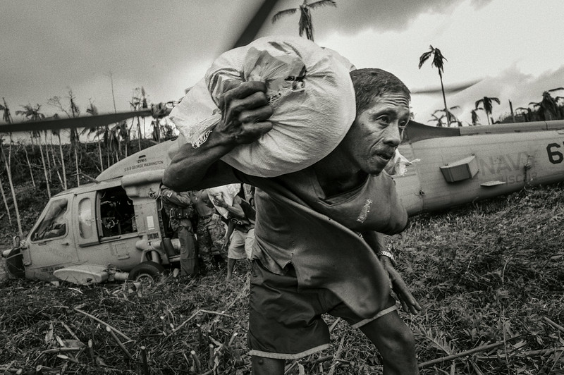 Description of  Local people helping unload a helicopter, the first aid to reach the remote community after Typhoon Haiyan. <br />Mahagnau village, Leyte, Philippines, November 20, 2013.<br />© Sean Sutton / MAG / Panos Pictures