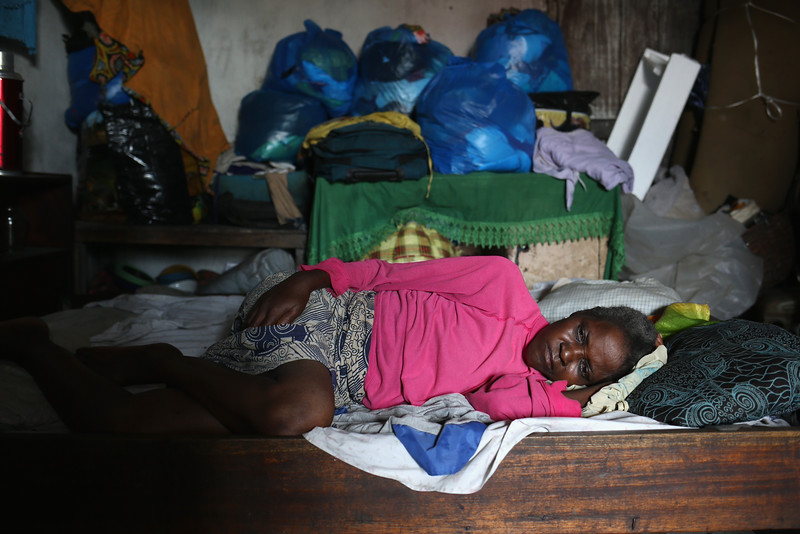 Description of  Tawah Fayiah, 54, lies sick in bed while awaiting transport from her one-room home to an Ebola isolation ward on August 15, 2014 in Monrovia, Liberia. People suspected of contracting the Ebola virus are being brought by health workers to a temporary facility - a closed primary school originally built by USAID, while larger facililities are being constructed to house the surging number of patients. The Ebola epidemic has killed more than 1,000 people in four West African countries.  (Photo by John Moore/Getty Images)