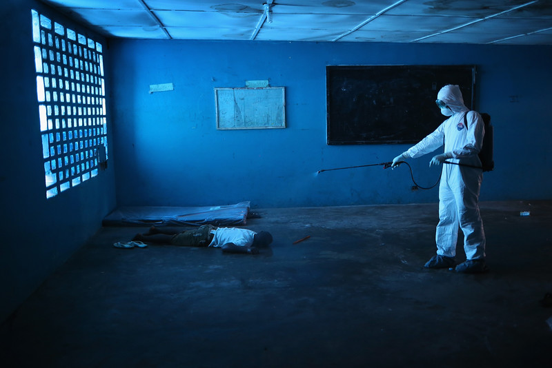 Description of  A Liberian health worker disinfects a corpse after the man died in a classroom now used as Ebola isolation ward on August 15, 2014 in Monrovia, Liberia. People suspected of contracting the Ebola virus are being sent by health workers to the center, a closed primary school originally built by USAID. The Ebola epidemic has killed more than 1,000 people in four West African countries.  (Photo by John Moore/Getty Images)