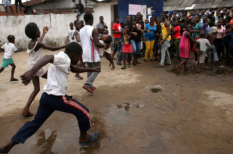 """Description of  A man carries out a girl from an Ebola isolation center as a mob overruns the facility in the West Point slum on August 16, 2014 in Monrovia, Liberia. A crowd of several hundred people, chanting, """"No Ebola in West Point,"""" crashed through the gates and took out the patients, many saying that the Ebola epidemic is a hoax. The center, a closed primary school originally built by USAID, was being used by the Liberian Health Ministry to temporarily isolate people suspected of carrying the virus. Some 10 patients had """"escaped"""" the building the night before, according to a nurse there, as the center had no medicine to treat them. The Ebola epidemic has killed more than 1,000 people in four West African countries, with Liberia now having the most deaths.  (Photo by John Moore/Getty Images)"""