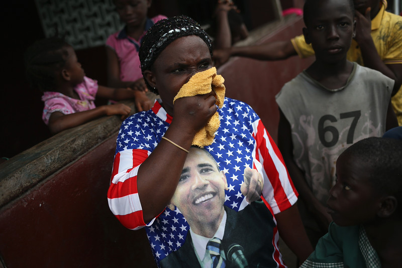"""Description of  A woman wipes her nose after protesters drove out an Ebola burial team who had come to collect the bodies of four people who had died overnight in the West Point slum on August 16, 2014 in Monrovia, Liberia. A crowd of several hundred local residents, chanting, """"No Ebola in West Point,"""" drove away the burial team and their police escort, who fired warning shots in the air. The mob then forced open an Ebola isolation ward and took the patients out, many saying that the Ebola epidemic is a hoax. The isolation center, a closed primary school originally built by USAID, was being used by the Liberian health ministry to temporarily isolate people suspected of carrying the virus. Some 10 patients had """"escaped"""" the building the night before, according to a nurse, as the center had no medicine to treat them. The Ebola epidemic has killed more than 1,000 people in four West African countries, with Liberia now having the most deaths.  (Photo by John Moore/Getty Images)"""