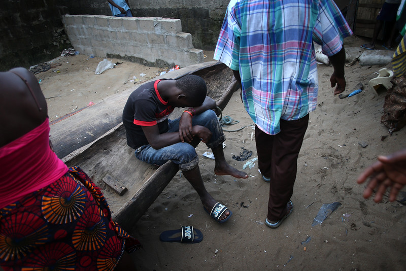 Description of  A young man slumps in a slum on August 15, 2014 in Monrovia, Liberia. Poor sanitation and close living quarters have contributed to the spead of the Ebola virus, which is transmitted through bodily fluids. The epidemic has killed more than 1,000 people in four West African countries.  (Photo by John Moore/Getty Images)