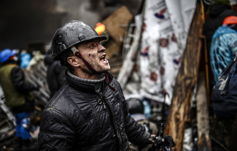 "Description of  A protester stands behind barricades during clashes with police on February 20, 2014 in Kiev. Ukraine's embattled leader announced a ""truce"" with the opposition as he prepared to get grilled by visiting EU diplomats over clashes that killed 26 and left the government facing diplomatic isolation. The shocking scale of the violence three months into the crisis brought expressions of grave concern from the West and condemnation of an ""attempted coup"" by the Kremlin. AFP PHOTO / BULENT KILIC"