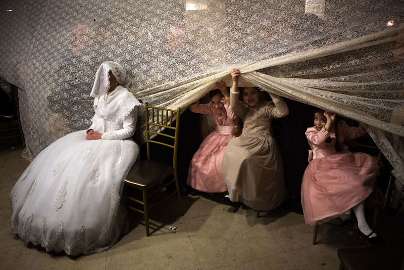 Description of  Children peep from behind a curtain next to Jewish ultra-orthodox bride Rivka Hannah (Hofman) during the Mitzvah Tans dance ritual following her wedding in an ultra-orthodox neighborhood of Jerusalem on February 18, 2014. During the Mitzvah Tans dance ritual the bride will dance with members of the community, family and with her groom at the end of the wedding ceremony. AFP PHOTO/MENAHEM KAHANA