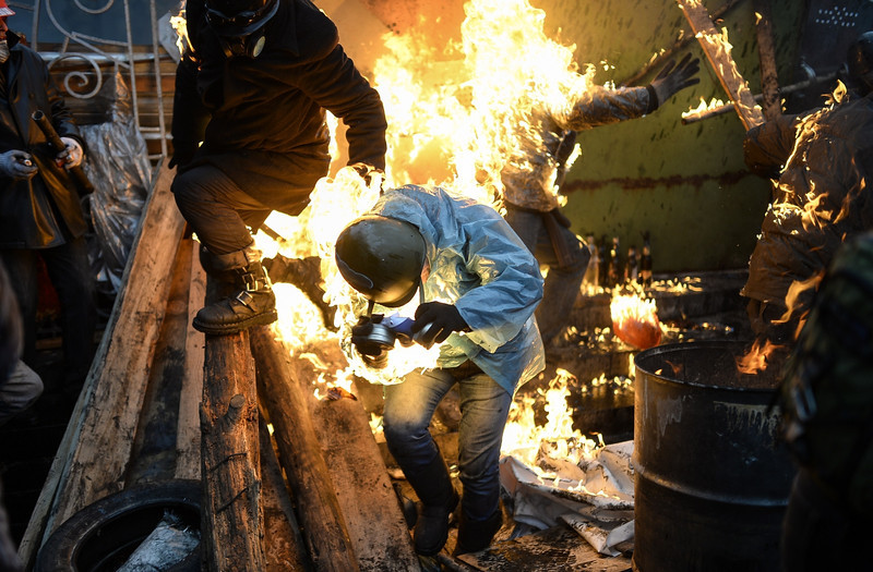 "Description of  Protesters catch fire as they stand behind burning barricades during clashes with police on February 20, 2014 in Kiev. Ukraine's embattled leader announced a ""truce"" with the opposition as he prepared to get grilled by visiting EU diplomats over clashes that killed 26 and left the government facing diplomatic isolation. The shocking scale of the violence three months into the crisis brought expressions of grave concern from the West and condemnation of an ""attempted coup"" by the Kremlin. AFP PHOTO/BULENT KILIC"