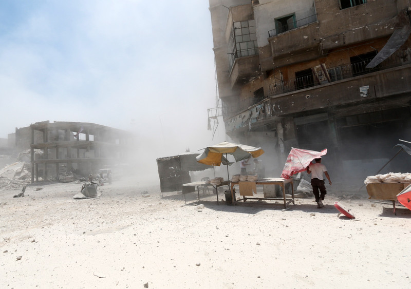 Description of  A Syrian street vendor carries an umbrella walking amid dust following a reported barrel-bomb attack by Syrian government forces on July 7, 2014 in the Tariq al-Bab neighbourhood in the northern city of Aleppo. The opposition Syrian National Coalition said on July 6, 2014 that regime forces are preparing to launch a major assault on rebel-held areas of Aleppo. AFP PHOTO /AMC / ZEIN AL-RIFAI