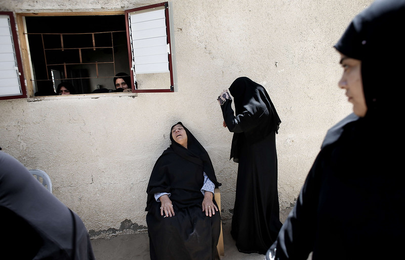 Description of  Female members of the al-Kaware family grieve during the funeral for 7 killed members of the family in Khan Yunis, in the Gaza Strip, on July 9, 2014. The father al-Kaware, a member of the Fatah movement, and his 6 young sons were all killed the day before in an Israeli air strike that targeted their home.  AFP PHOTO / THOMAS COEX