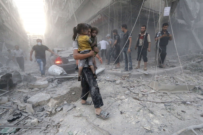 "Description of  A Syrian man carries two girls covered with dust following a reported air strike by government forces on July 9, 2014 in the northern city of Aleppo. According to the Syrian Observatory for Human Rights, by May some 2,000 civilians including 500 children had been killed in the daily air strikes, which rights groups have condemned as a ""war crime"" for failing to discriminate between military and civilian targets. AFP PHOTO /AMC/ZEIN AL-RIFAI"
