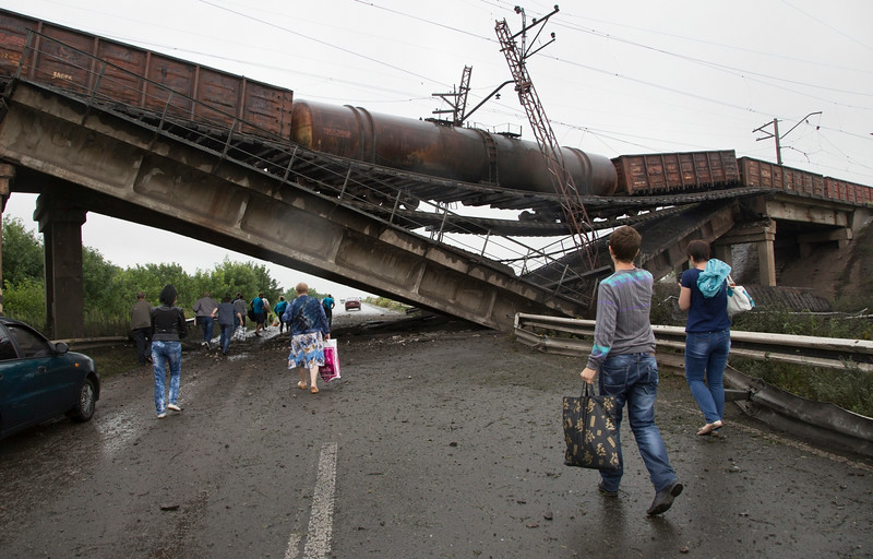 Description of  People walk under a destroyed railroad bridge over a main road leading into the east Ukraine city of Donetsk, near the village of Novobakhmutivka,  20 km North from the city of Donetsk, eastern Ukraine Monday, July 7, 2014. The bridge has been destroyed, blocking a key access route to the rebel-held city. (AP Photo/Dmitry Lovetsky)