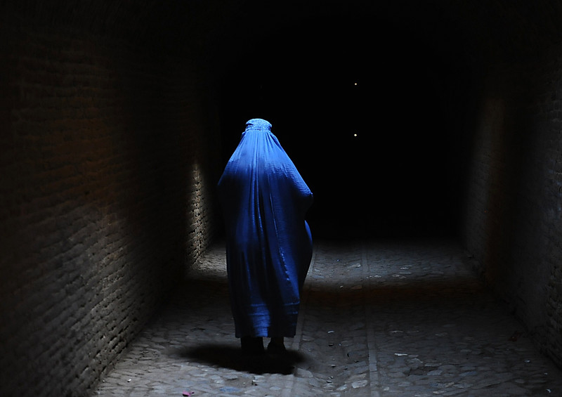 Description of  A burqa-clad Afghan woman walks in the old part of Herat on July 10, 2014. Afghanistan remains at war, with civilians among the hardest hit as the Taliban wage an increasingly bloody insurgency against the government. AFP PHOTO/AREF KARIMI