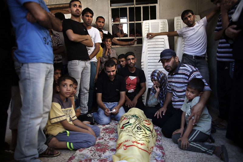 Description of  Relatives and friends of the al-Kaware family mourn over one of the 7 members of the family during their funeral in Khan Yunis, in the Gaza Strip, on July 9, 2014. The father, a member of the Fatah movement, and his 6 young sons were all killed the day before in an Israeli air strike that targeted their home.  AFP PHOTO / THOMAS COEX