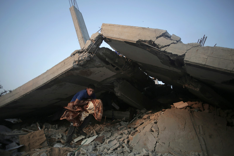 Description of  Palestinians try to salvage what they can of their belongings from the rubble of a house destroyed by an overnight Israeli airstrike in Gaza City Tuesday,  July 8, 2014. Israel launched what could be a long-term offensive against the Hamas-ruled Gaza Strip on Tuesday, the military said, striking at least 50 sites in Gaza by air and sea and mobilizing troops for a possible ground invasion in order to quell rocket attacks on Israel. (AP Photo/Khalil Hamra)